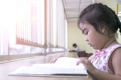 Die Kinder sind Lesebücher in der Bibliothek stockfotografie