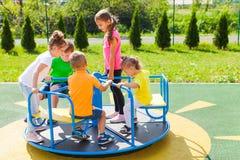 Die Kinder spinnen das Karussell der Reihe nach stockfoto