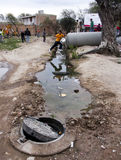 Die Kinder springend über einen Abzugsgraben durch Abwasser Lizenzfreies Stockfoto