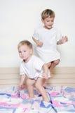 Die Kinder springend auf Bett der Muttergesellschafts Stockbilder