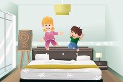 Die Kinder springend auf das Bett Lizenzfreies Stockfoto