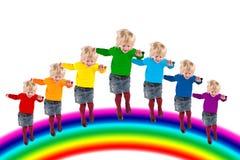 Die Kinder springend auf Regenbogen, Collage lizenzfreie stockfotografie