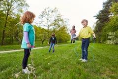 Die Kinder springend, den Park im Sommer einzufangen stockfoto