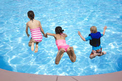 Die Kinder springend in den Swimmingpool Stockfotos