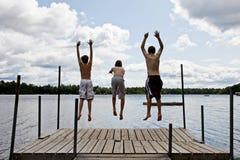 Die Kinder springend in See lizenzfreies stockbild