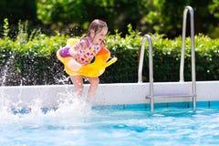 Die Kinder springend in Swimmingpool lizenzfreie stockfotografie
