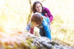 Die Kinderaufstiege auf dem Flussstein Stockfoto