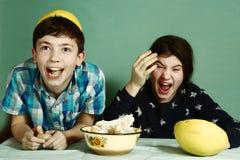 Die Kindergeschwister, die Traubenfrucht abziehen, stellen lustigen Hut her lizenzfreies stockbild