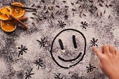 Die Kinderhand, die glückliches Gesicht in den Weihnachtsplätzchen zeichnet, bemehlen Lizenzfreie Stockbilder