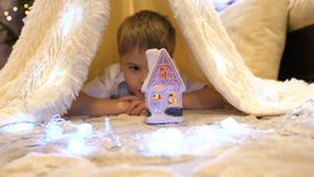 Die Kinderspiele im Kinderzimmer in einem Zelt mit einem Weihnachtslicht Glückliche Kindheit stockfotos