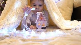 Die Kinderspiele im Kinderzimmer in einem Zelt mit einem Weihnachtslicht Glückliche Kindheit lizenzfreies stockbild