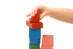 Die Kindhand baut Aufbau von den Würfeln auf Stockbilder