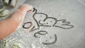 Die Kindhand zeichnet auf Mehl Weicher Fokus Sie zeichnete das sch?ne Herz mit ihren Fingern stock video