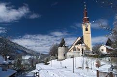 Die Kirche von Tarvisio während des Winters mit Schnee lizenzfreie stockfotos