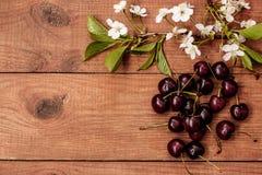 Die Kirschblüten und -kirschen auf einem Holztisch Stockfoto