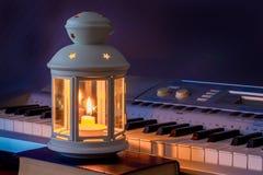 Die Klavierschlüssel werden durch eine Kerzenlichtlampe beleuchtet Ausführung von Musik mit candles_ stockfoto