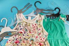 Die Kleidung der Kinder mit Aufhängern auf einem blauen Hintergrund stockfotografie