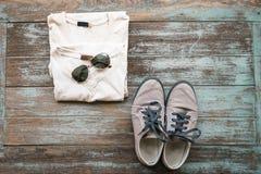Die Kleidung, die Sonnenbrille und die Schuhe des Mannes legen auf hölzernen Weinlesehintergrund, Stockfotografie