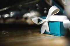 Die kleine blaue Geschenkbox, hölzerne Weinlese maserte Hintergrund Stockfotos