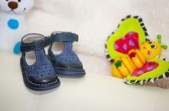 Die kleine blauen Babyschuhe und Spielzeugschmetterling Lizenzfreie Stockfotos