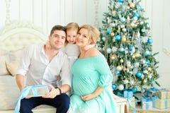 Die kleine blonde Tochter, die mit glücklichem Vater und schwangerer Mutter auf Bett nahe sitzt, verzierte Weihnachtsbaum Lizenzfreie Stockfotos