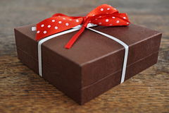 Die kleine braune Geschenkbox, die mit weißem Band und Rot eingewickelt wurde, punktierte Bogen auf dem hölzernen Hintergrund als Lizenzfreie Stockfotos