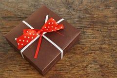 Die kleine braune Geschenkbox, die mit weißem Band und Rot eingewickelt wurde, punktierte Bogen auf dem hölzernen Hintergrund als Lizenzfreie Stockfotografie