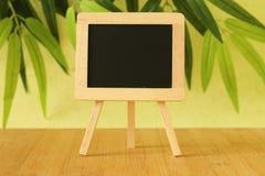 Die kleine leere Tafel, zum einer Mitteilung zu schreiben warf auf einem Gestell auf einem Bretterboden mit einem grünen Laubhint Stockbilder