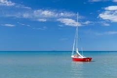 Die kleine Yacht wird auf dem ruhigen See festgemacht Stockbilder