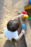 Die kleinen Kinderspiele in einem Sandkasten mit Spielwaren Lizenzfreies Stockbild