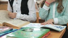 Die kleinen Mädchen, die am Schreibtisch sitzen, schlägt Seiten des Buches leicht stock video