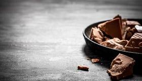 Die Klumpen der Schokolade auf der alten Platte Stockbilder