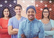 Die Kollegen, die mit den Armen stehen, kreuzten gegen amerikanische Flagge im Hintergrund Stockfotografie