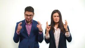 Die Kollegen kreuzten ihre Finger und schlossen ihre Augen Ende des Abkommens aktiv erfolgreich betend Lizenzfreies Stockfoto
