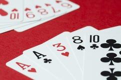 Die Kombination von Karten im Schürhaken auf einem roten Hintergrund lizenzfreie stockfotografie