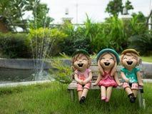 Die konkrete Statue mit drei Mädchen sitzen im Garten Stockbild