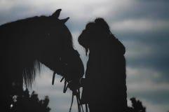 Die Kontur eines Mädchens und ihres Pferds Stockbild