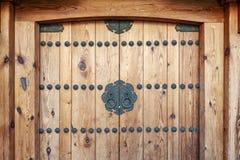 Die koreanischen Holzt?rplatten, die mit altem schwarzem metallischem Ring verziert werden, behandelt an einem Haus im alten Dorf lizenzfreies stockbild