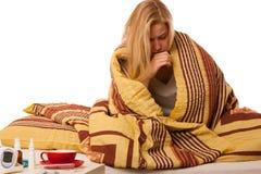 Die kranke Frau, die auf dem Schlechten eingewickelt wird in einem umfassenden Gefühlskranken sitzt, hat Stockbild