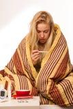 Die kranke Frau, die auf dem Schlechten eingewickelt wird in einem umfassenden Gefühlskranken sitzt, hat Lizenzfreie Stockfotos