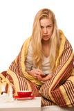 Die kranke Frau, die auf dem Schlechten eingewickelt wird in einem umfassenden Gefühlskranken sitzt, hat Lizenzfreie Stockfotografie