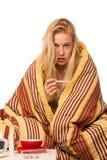 Die kranke Frau, die auf dem Schlechten eingewickelt wird in einem umfassenden Gefühlskranken sitzt, hat Lizenzfreies Stockfoto
