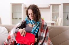 Die kranke junge Frau, die zu Hause leidet stockfoto