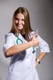 Die Krankenschwester mit einer Spritze zeigt einen Daumen Lizenzfreie Stockbilder