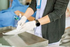 Die Krankenschwester mit vielen Medizin ist, säubernd vorbereitend oder den Stich ihres Frauenpatienten nach Chirurgie in der ged Stockfotos