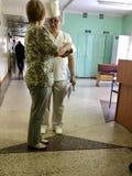 Die Krankenschwester spricht mit dem Krankenhauspatienten im Korridor der Abteilung Lizenzfreies Stockfoto