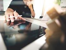 Die kreative Hand, die digitale Tablette bearbeiten und das Holz verwirrt mit Laptop Lizenzfreie Stockfotografie