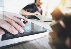 Die kreative Hand, die digitale Tablette bearbeiten und das Holz verwirrt mit Laptop Stockbild