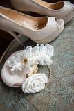 Die Kupplung der Frauen mit Weißrose, -schuhen und -strumpfband auf Messingbehälter mit einer Verzierung Lizenzfreies Stockfoto