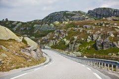 Die kurvenreiche Straße zwischen den felsigen Bergen in Norwegen Stockfotografie